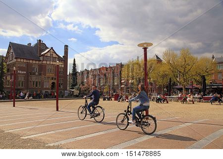 AMSTERDAM, NETHERLANDS - MAY 4, 2016: Local people on bicycle in historical center in Amsterdam, the Netherlands. Bicycles outnumber people in Amsterdam: 760000 citizens and nearly a million bikes.