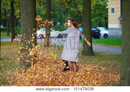 Young charming girl spinning in a fun autumn waltz throwing fallen leaves up between the trees in one of St. Petersburg courtyards.