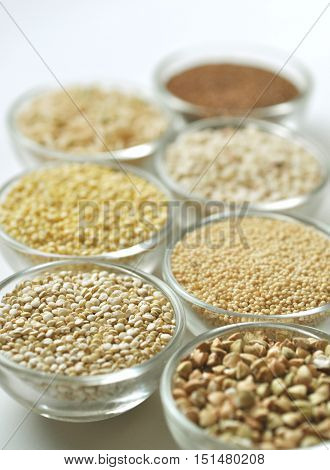 various gluten-free cereal grains in small bowls, side view