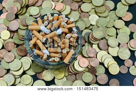 Buying cigarettes lose money and health . cigarette, money and ashtray .