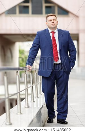 portrait of handsome young businessman in blue suit and red tie walking outdoors