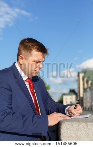 half growth portrait of handsome young businessman in suit outside, signs documents