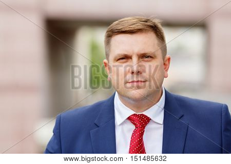Portrait of handsome young businessman in suit walking outdoors, close-up
