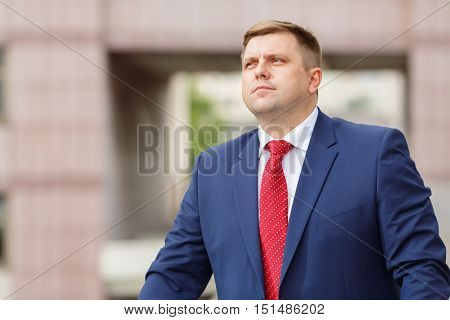 half growth portrait of handsome young businessman in suit walking outdoors