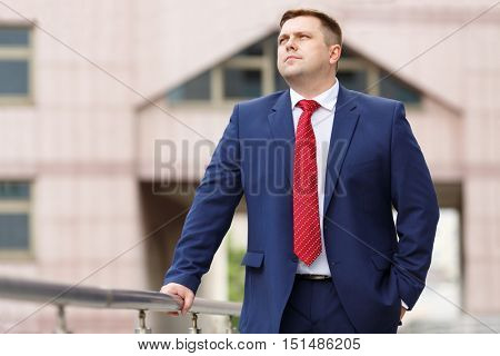 half growth portrait of handsome young businessman in suit walking outdoors, looking away