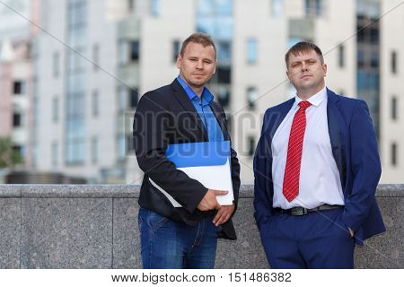 Two successful young businessman well-dressed standing together outside