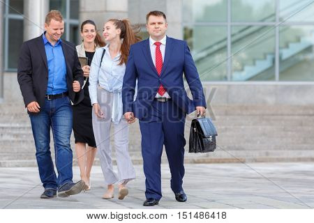 four business people (two man and two woman) walking down street on background of business centers, communicate