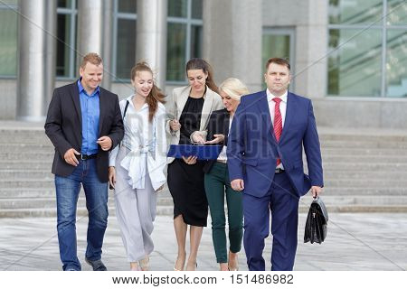 five business people walking down street on background of business centers