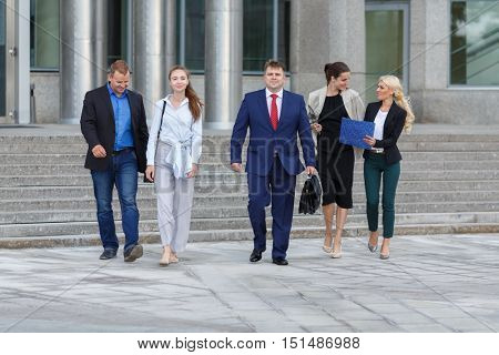 five young attractive business people walking down street on background of business centers