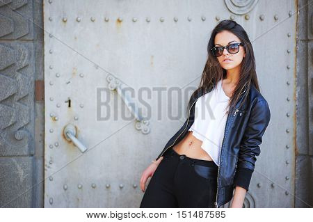 Young beautiful brunette girl in a short white tank top leather jacket jeans and sunglasses standing on the background of the iron gates.