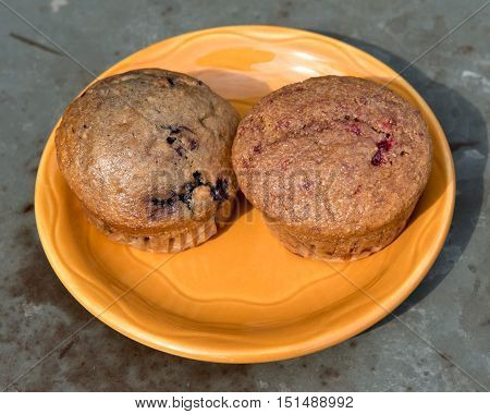Strawberry and cranberry muffins on ceramic plate and metal table