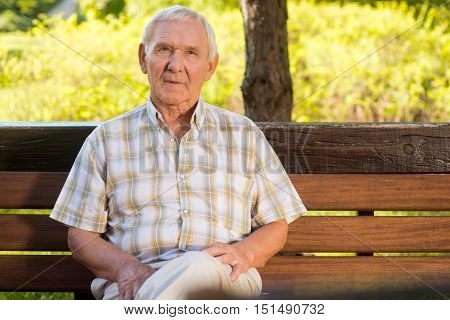Thoughtful senior man. Old male sitting on bench. Rethink all decisions. Past shapes the future.