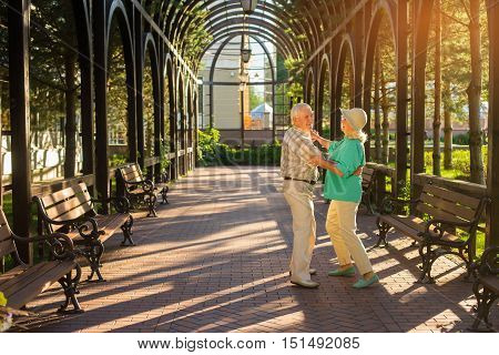 Senior couple dancing. Elderly people are smiling. Waltz in the park. Choose an active lifestyle.
