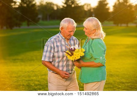 Senior couple on meadow background. Smiling elderly woman holds bouquet. Our golden wedding. I'll stay devoted to you.