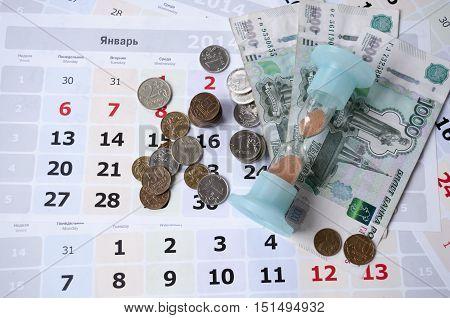 Hourglass and money lie on calendar sheets