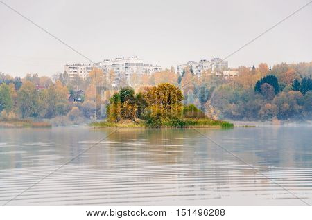 Fog on the lake Senezh in Solnechnogorsk fall in calm weather. The views of Raspberry island and high-rise residential houses of the city. Autumn water landscape