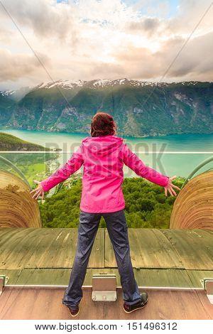 Tourist woman on Stegastein viewpoint enjoying Aurland fjord view in evening time Sogn Og Fjordane Norway