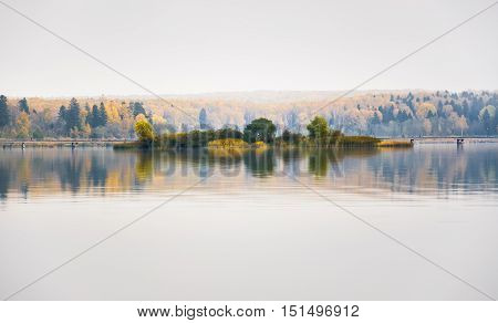 Fog on the lake Senezh in Solnechnogorsk fall in calm weather. Views of the picturesque island and a pedestrian bridge. Autumn water landscape