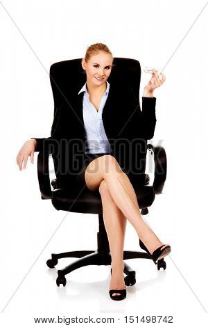 Business woman sitting on wheel chair and holding toy plane