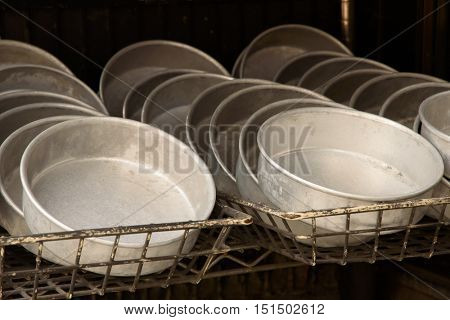 Used circular baking pans for sale at a second hand restaurant supply store.