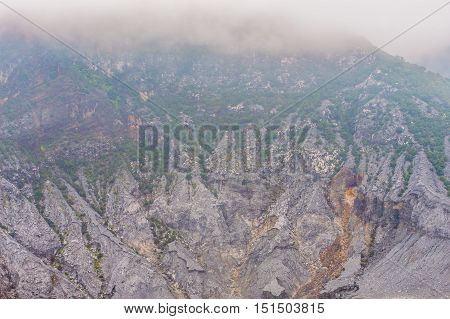 Rock formations inside a volcano caldera covered by large cloud bank