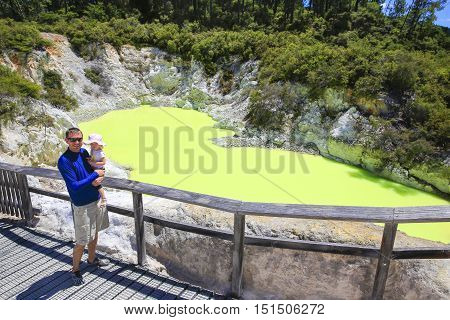 Young Tourist With A Child. Devil's Bath Pool In Waiotapu Thermal Reserve