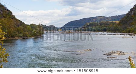 Shenandoah River and Potomac River meet each other near Harpers Ferry West Virginia USA. Low river waters with rocks with Appalachian Mountains on horizon.
