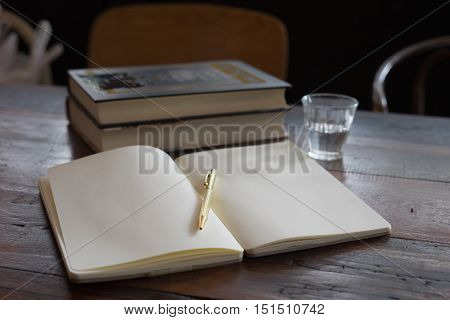 water glass wooden notebook golden pen big textbook on wooden tray and table at coffee time /notebook textbook and golden pen