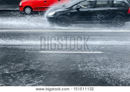 Cars Driving Through Water Puddles On City Road With Water Spraying