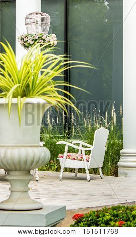 White chair and flower pot on relaxing space in cozy garden on summer.