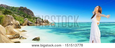 Beautiful young woman in happy mood, looking at tropical beach. Travel and relaxation concept