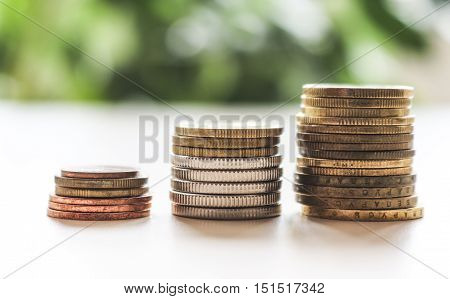 The concept of saving money . Piles of money on green blurred background.