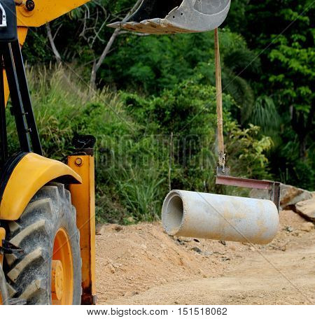 power shovel lifting heavy concrete water pipe section while doing road construction near Songkhla, Thailand