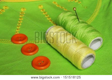 Sewing accessories. Closeup of yellow and green thread and orange buttons on light green background.