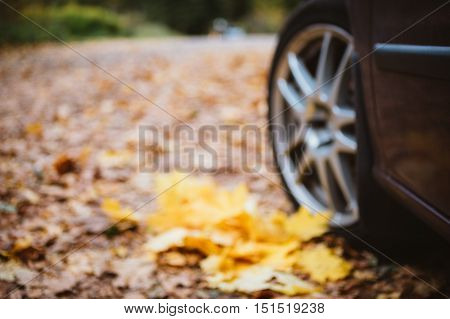 Blurred image of car wheel closeup against fallen leaves in autumn park