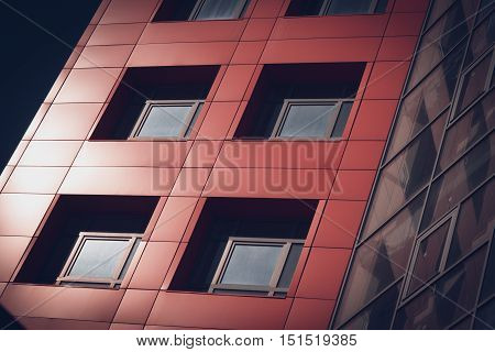 horizontal image of the red  facade of a modern building with square windows and deep shadows filter