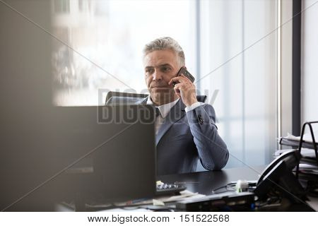 Senior businessman on the phone and making a phone call from his desk