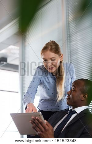 Young woman showing something on digital tablet to male colleague in office