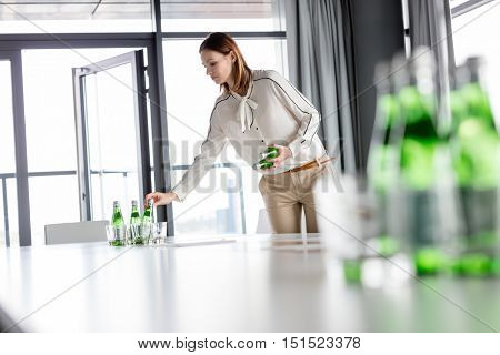 Young businesswoman arranging water bottles on table in meeting room