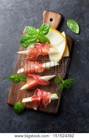 Fresh melon with prosciutto and basil. Antipasti. Top view on dark stone table