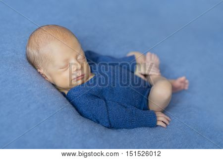 sleepy newborn baby in blue jumpsuit smiling and holding his leg