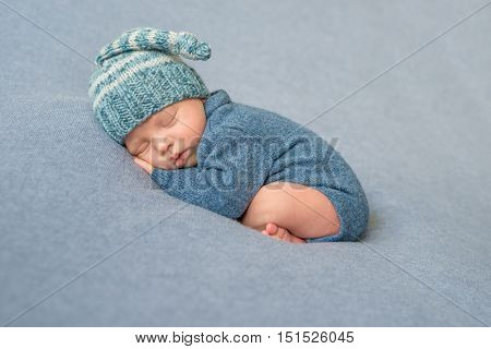 sleeping newborn baby in blue knitted jumpsuit and hat with crossed legs