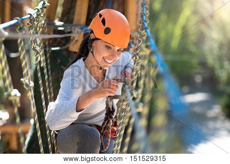 Safety equipment in use. Beautiful positive young woman sitting on the rope road and locking a mountain carabiner while using safety equipment