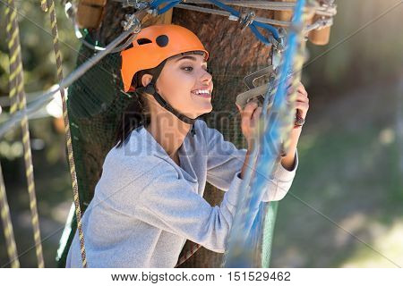 Safety is important. Pleasant cheerful careful woman sitting and looking at the mountain carabiner while checking it