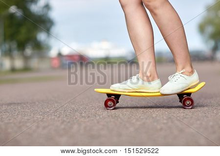 skateboarding, leisure, extreme sport and people concept - close up of teenage girl legs riding short modern cruiser skateboard on road