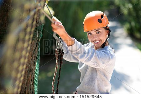 Adventure climbing. Positive happy cute woman holding her hand up and holding on to the rope while enjoying adventure climbing