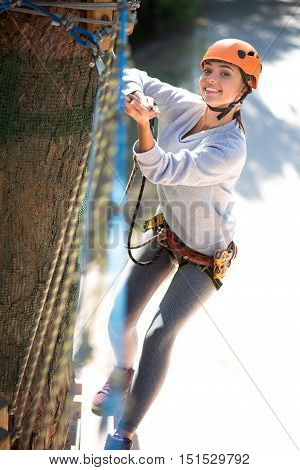 I like extreme sport. Active good looking delighted woman holding on to the rope and moving forward while taking pleasure in the high risk activities