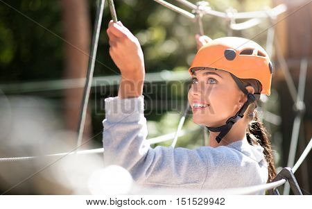 In the high wire adventure park. Cute joyful young woman looking somewhere up and smiling while clambering