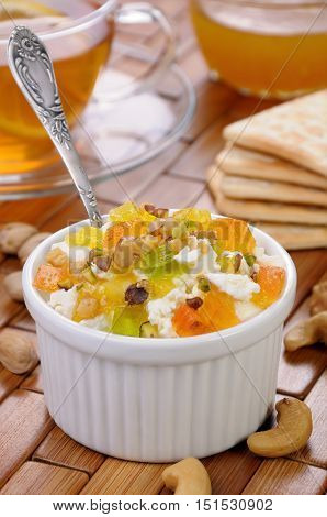 portion of cottage cheese with jam and marmalade slices nuts pistachios