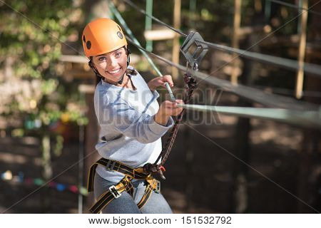 Try not to fall. Positive good looking slender woman moving forwards with the help of the rope and smiling while being high above the ground